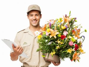Portrait of a happy delivery man holding a bouquet of flowers and clipboard. Horizontal shot. Isolated on white.